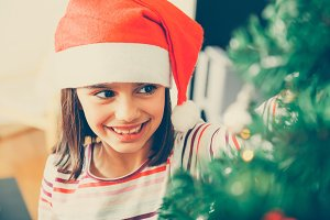 Little girl decorating tree