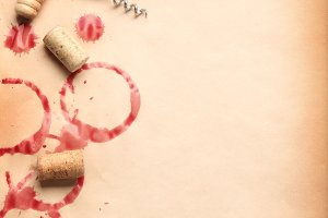 Wine circles from the bottle on old paper with a corkscrew and stoppers.