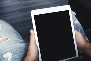 Man holding a white Ipad