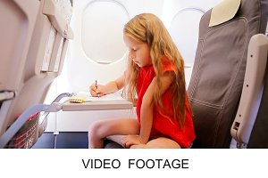 Little girl in plane with pencils