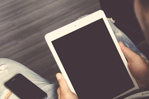 Man holding a white Ipad and Iphone
