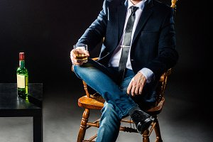 The happy businessman holding glass of whiskey and looks in the camera. Studio shot.