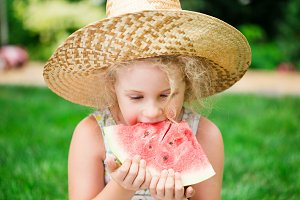 Cute little blonde girl eating watermelon, summertime outdoor