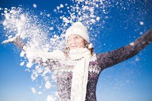 Young woman having fun with snow