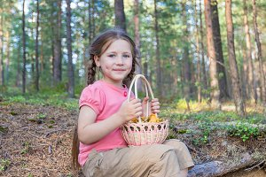 Pretty child girl with mushroom basket in the forest