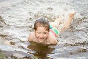 Little girl swim in lake outdoors