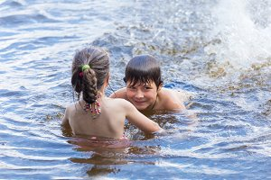 Little boy teaches sister to swim in