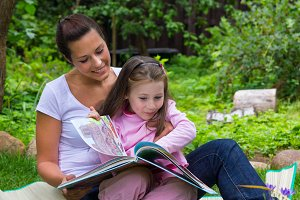 Woman and daughter read book