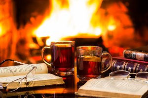 Two glasses of hot drink wine, antique books, fireplace