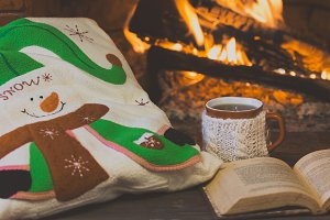 Antique books, tea, pillow, fireplace as background. Christmas, winter concept