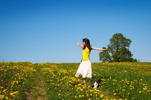 Young woman on a meadow of dandelion spring time