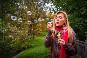 Woman blowing soap bubbles outdoors