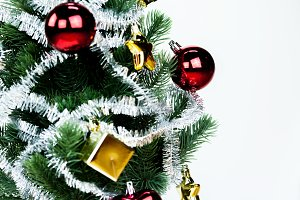 Close-up of christmas tree decorated with ornaments in white isolated background - with copyspace