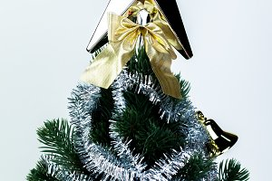 Top of Christmas tree decorated with star in bright white isolated background