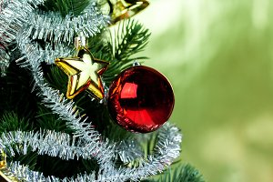 Close-up of christmas tree decorated with ornaments in rich shiny gold background - with copyspace