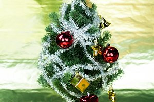 Christmas tree decorated wiith ornaments in rich gold shiny background - full length