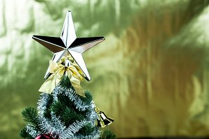 Top of Christmas tree decorated with star in bright golden shiny background