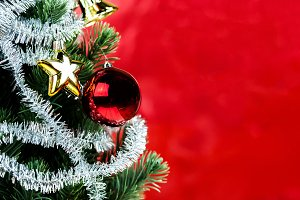 Close-up of christmas tree decorated with ornaments in rich shiny red background - with copyspace