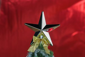 Top of Christmas tree decorated with star in bright red shiny background