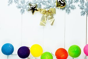 Christmas themed ornaments and colorful ball lights on white clean wood background - with copy space
