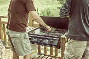 Men cleaning the barbecue