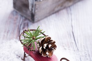 Christmas composition with sleigh, pinecone and decoration