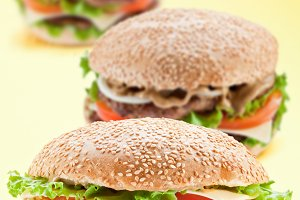 Three delicious hamburger on a yellow background