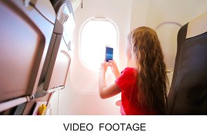 Girl sitting near window in airplane