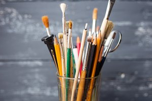 Various paint brushes in glass