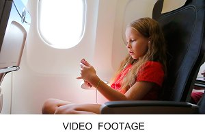 Cute kid with phone in airplane