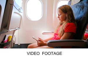 Adorable girl with phone in airplane