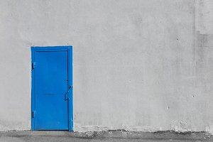 Blue metal door on gray stucco building wall