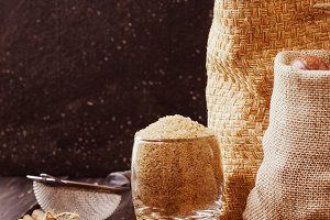 Thatched brown sugar in a cup, wooden background, selective focus