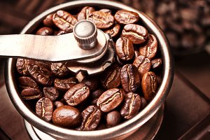 Roasted coffee beans are ground in a coffee grinder.