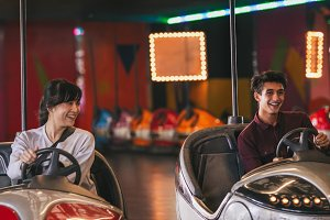 Young friends riding bumper cars