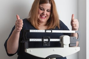 Woman celebrating on the scale