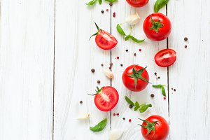 Tomatoes, basil and garlic on white wooden table