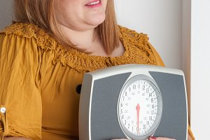 overweight woman holding scale