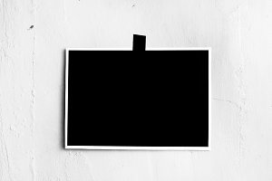 Blank black poster hanging on a tape on the wall. Template backg