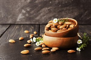 raw almonds on wooden bowl, selective focus, space for text