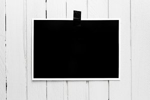 Blank black poster hanging on a tape on white wooden plank wall.