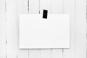 Blank white poster hanging on a tape on white wooden plank wall.