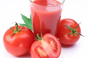 Full glass of fresh tomato juice and tomatoes are round the galss.