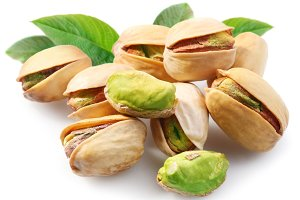 Pistachios with leaves on white background