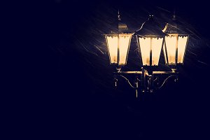Street lamps in snowfall close up photo. Tinted photo