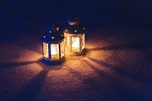 Two Lantern with burning candle on snow in the evening. Tinted p