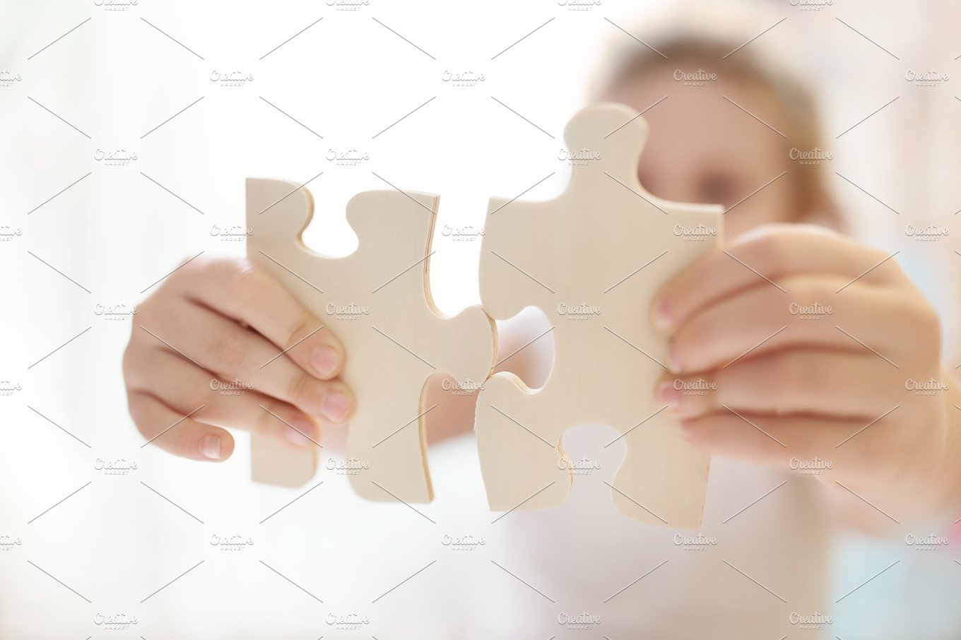 child girl holding two big wooden puzzle pieces hands connecting