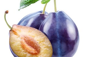 Plums with a slice and leaf on a white background.