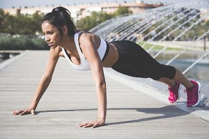 Sporty woman doing push-ups exercises
