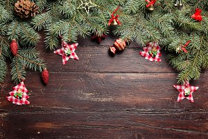 Christmas or New Year decoration background: fur-tree branches, colorful glass balls and glittering stars on wooden background, top view, copy space.